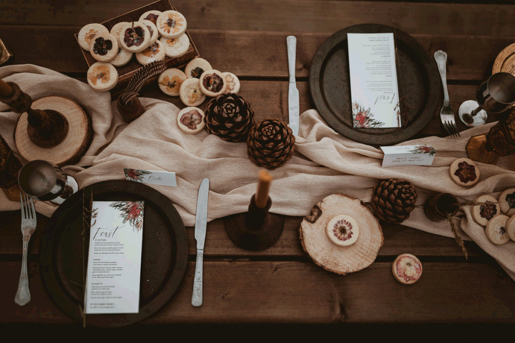 A wooden bench is laid with a pale mocha cloth runner, dark plates, silver cutlery,. amber goblet glasses and rustic decor finishing touches