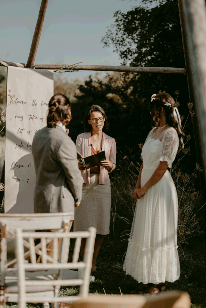 A male and female dressed in their wedding attire stand looking towards their celebrant, who is stood slightly back and between them. They are surrounded by natural decor