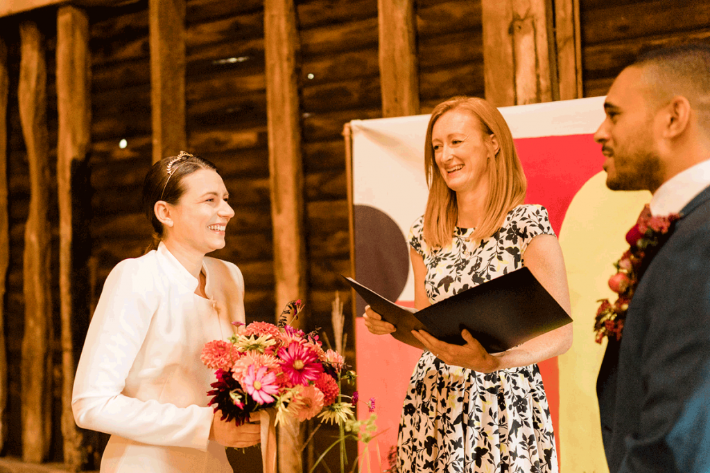 A wedding couple stand at the top of the aisle with their wedding celebrant, sharing a laugh mid ceremony