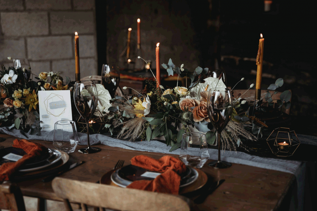 Concrete troughs are placed int he centre of a wooden wedding table, filled with foam free florals of whites, creams, oranges and yellows. The surrounding are darka nd they are accented by dark crockery and cutlery.