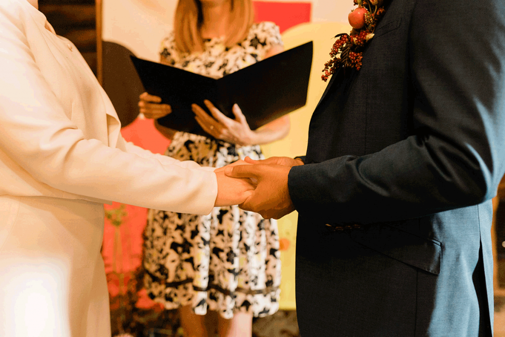 A couple hold hands during their wedding ceremony