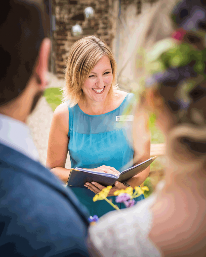 Kelly Hawes Independent Celebrant wearing a blue dress and framed by a wedding couple stood in the foreground of the image
