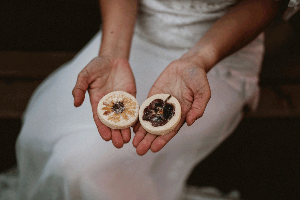 The hands of a white female hold 2 shortbread biscuit wedding favours with pressed flowers set into them as decoration. Below her hands you can see her white lace wedding dress