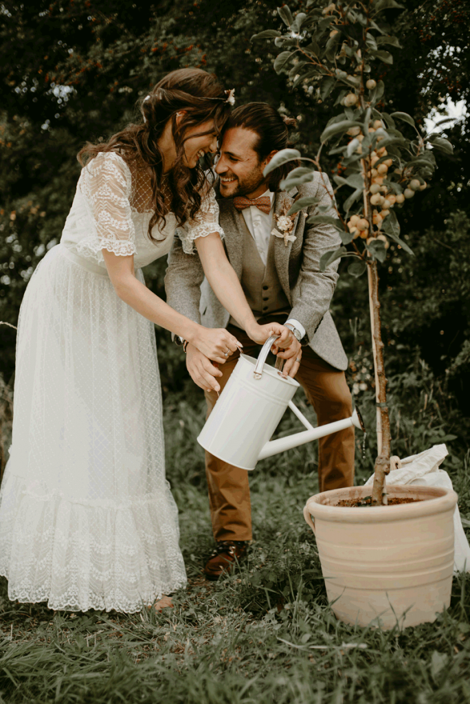 A newlywed couple plant a tree as part of their humanist wedding ceremony. They stand resting their heads together and smiling as they lean towards the tree with a watering can in hand