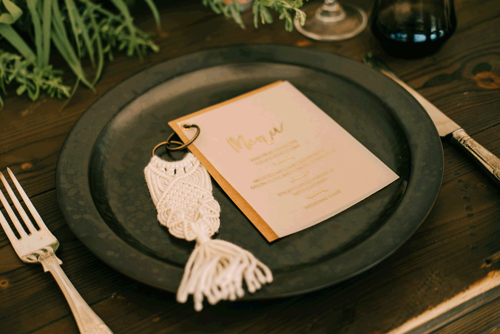 A vellum wedding menu is printed with gold foiling and has a gold card backsheet. They are held together with a marcrame keyring favour and placed upon a black mottled dinner plate
