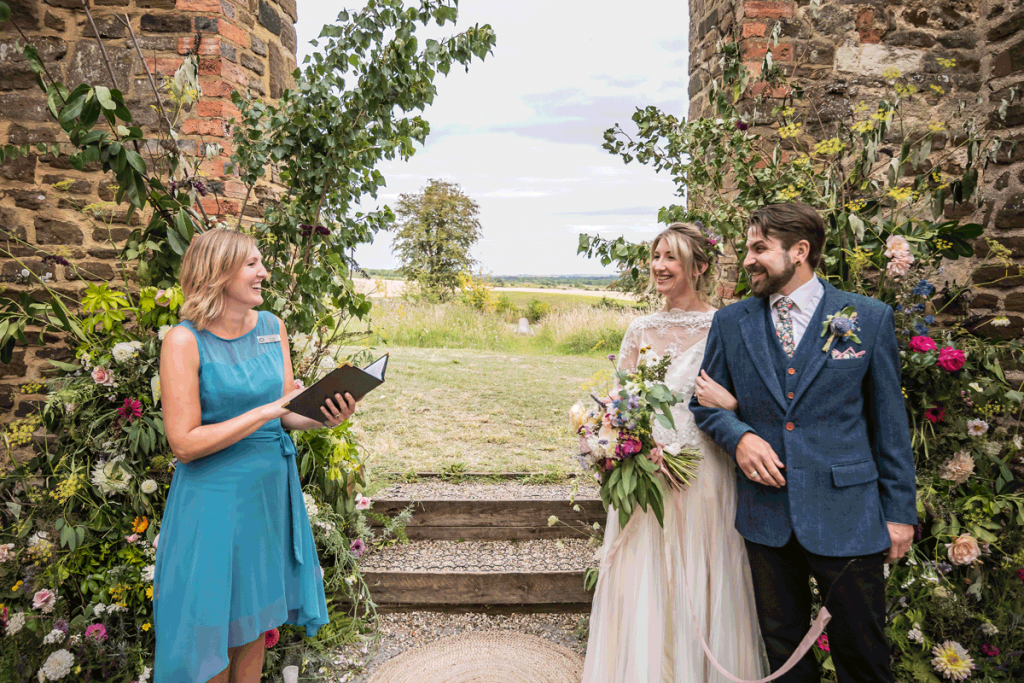 A celebrant stands within a ruined church building conducting a wedding ceremony, with a beautiful view through the arch beyond